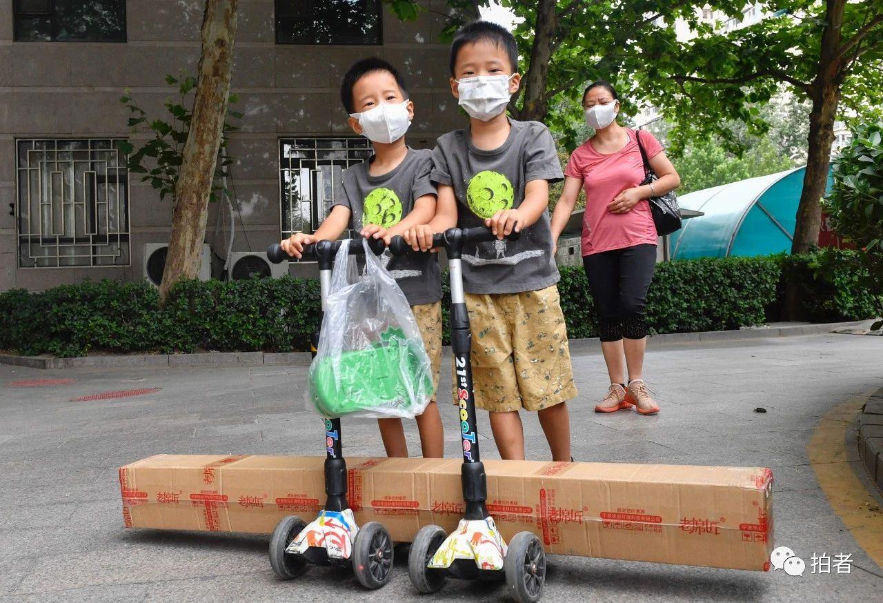 △6月17日,向阳区一小区,两名小同伙在家长的陪伴下,用滑板车取货。拍照/新京报记者吴宁