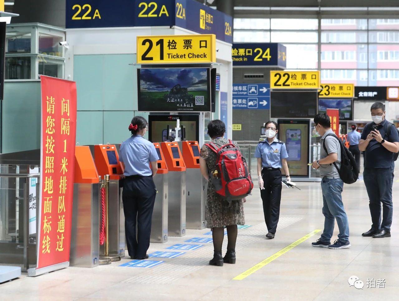 △6月17日,北京南站,事情职员提示搭客保持一米距离有序检票。拍照/新京报记者王贵彬