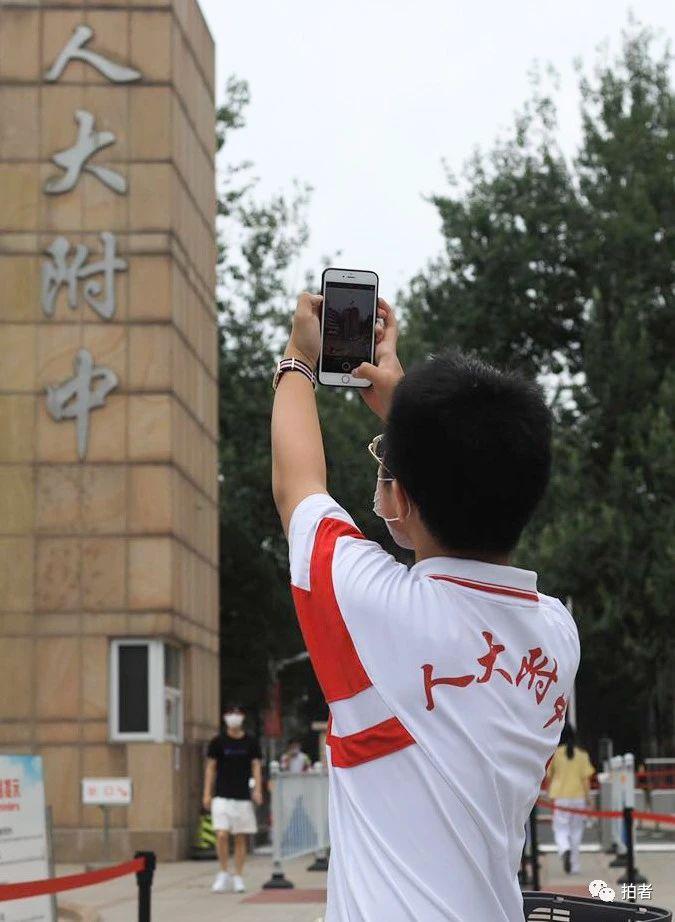 △6月17日上午,人大附中校门口,一名男生用手机拍下校门留念。拍照/新京报记者浦峰