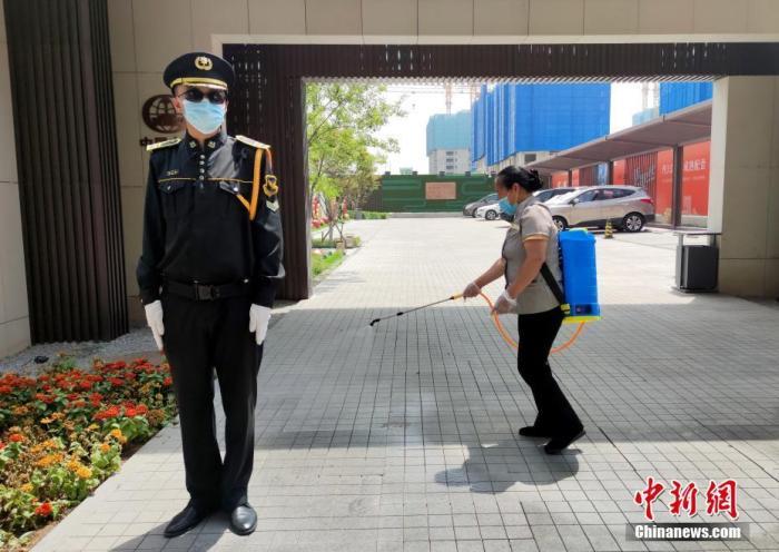 6月16日,北京花乡区域一售楼处外,事情职员正在举行防疫消毒。 中新社记者 张宇 摄