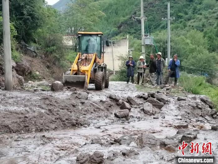 抢险职员正在清算门路上的泥浆和石头等。丹巴宣提供