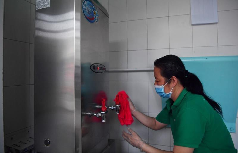 事情职员在对饮水装备举行消毒。新京报记者李木易摄