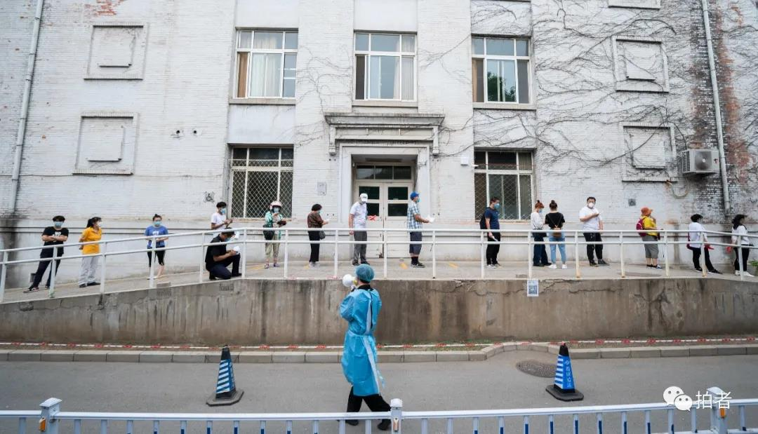 △6月17日,北京大学首钢医院,事情职员用喇叭提示前来举行核酸检测的人们保持平安间隔列队。