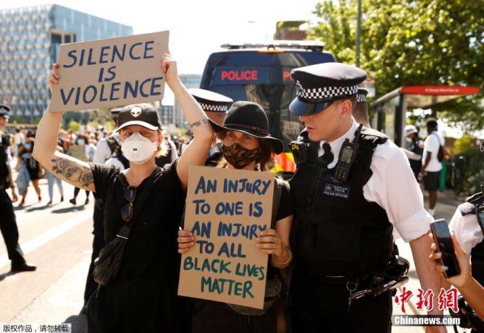 5月31日,英国伦敦,当地警察站在手持标语的抗议者身前。