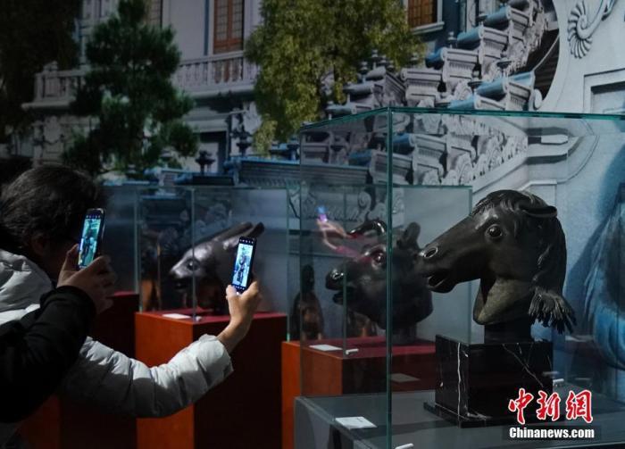 资料图:观众在马首铜像(右)前拍照。中新社记者 张兴龙 摄