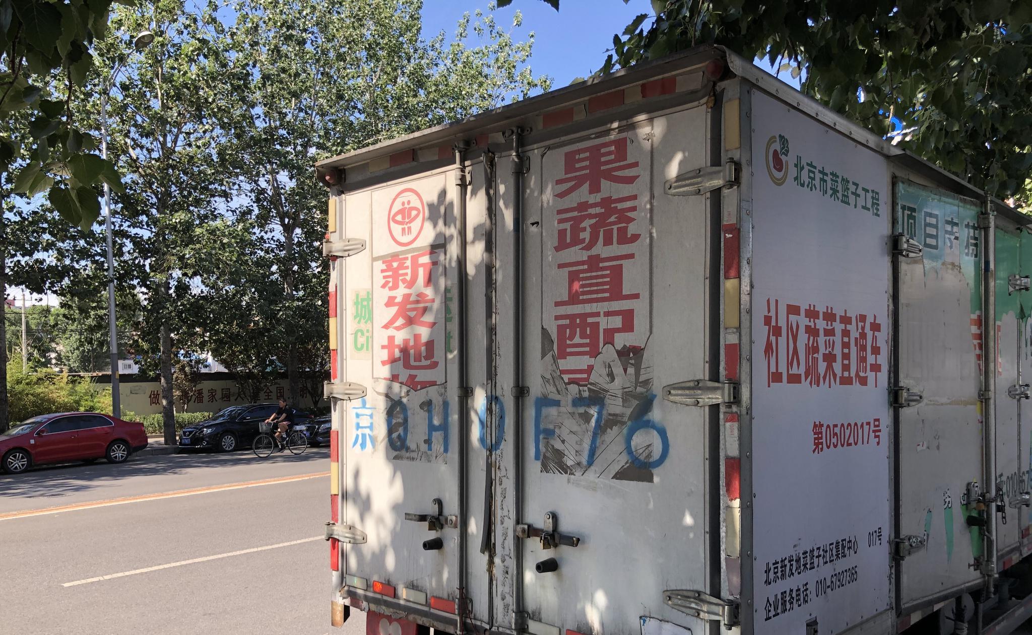 """北京某菜市场旁停靠的标有""""新发地""""的货车。汹涌消息记者 汤琪 图"""