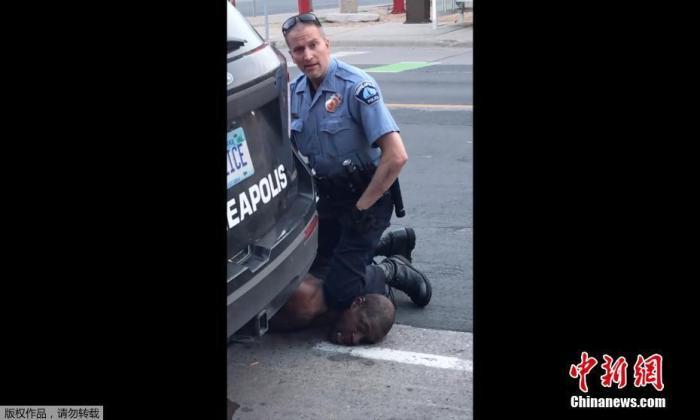 资料图:当地时间5月25日,美国明尼苏达州明尼阿波利斯市一名警察在逮捕非裔男子乔治·弗洛伊德时,将其按在地上,用膝盖顶住脖子。随后,弗洛伊德在被送往医院后不治身亡。(视频截图)
