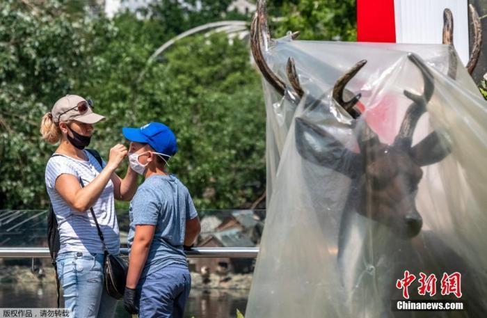 资料图:当地时间6月16日,俄罗斯莫斯科动物园重新开放,园区内戴口罩的女士为男孩儿调整口罩。