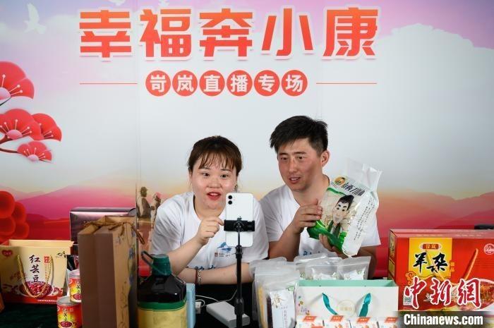 忻州市岢岚县大涧乡官庄村第一书记田亮(右)向网友推荐岢岚县农特产品。 韦亮 摄