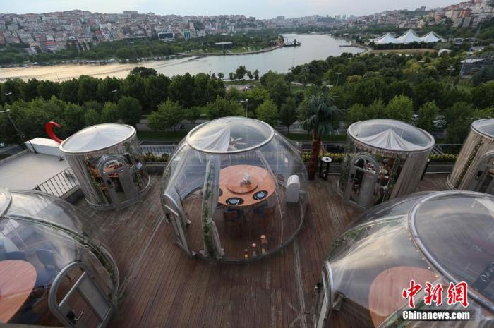 """当地时间2020年6月16日,土耳其伊斯坦布尔,为保持用餐期间""""社交距离"""",一家餐厅设置了""""圆顶""""形状的隔离用餐区。"""