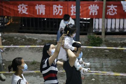 20日破晓1点,检测步队中,一名女童被人扛在肩上列队守候着。《中国谋划报》记者郝成摄