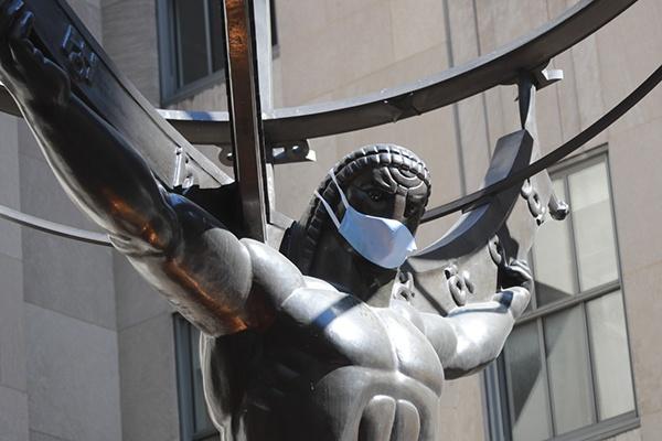 """6月22日,在美国纽约洛克菲勒中心,一座雕像被""""戴""""上口罩。新华社 图"""