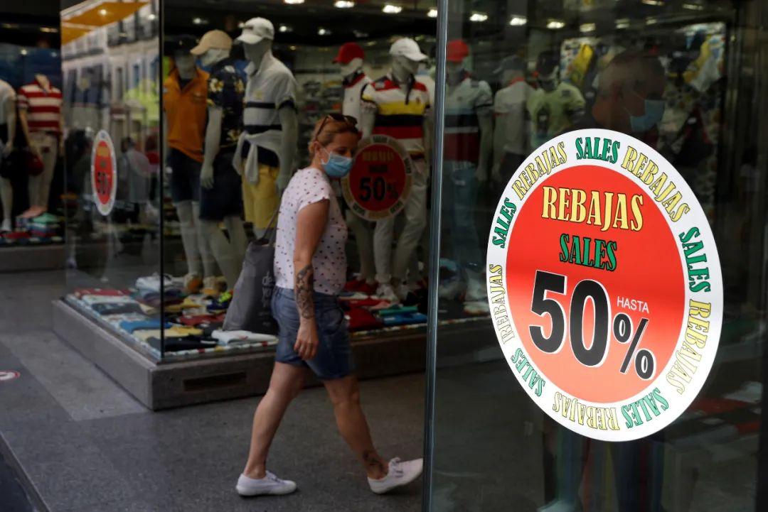 """▲一名顾客25日走进西班牙马德里市区的一家商店,商店橱窗上贴着写有""""低至五折""""的广告。(欧洲新闻图片社)"""