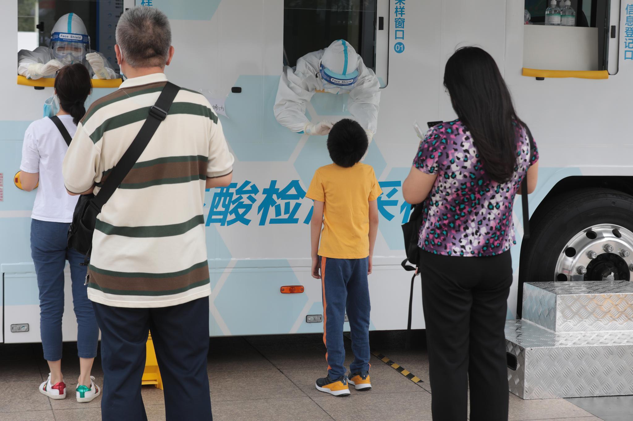 医护职员站在车厢中,通过窗口为市民收罗咽拭子。拍照/新京报记者 王嘉宁