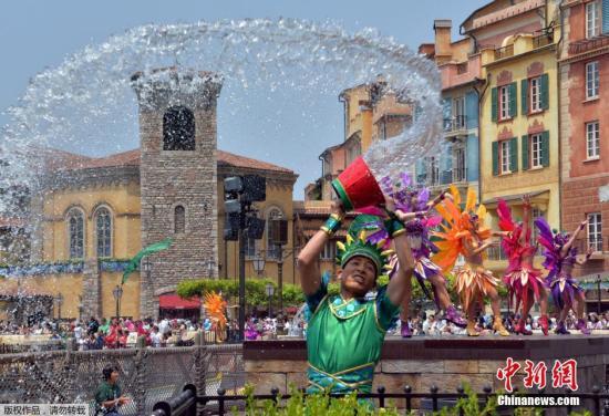 资料图:日本东京迪士尼乐园内的工作人员将一桶水泼向空中。