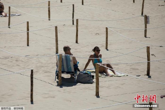 当地时间5月24日,在法国南部的拉格兰德莫特,在海滩上晒日光浴的人们躺在一个标志明显的区域内,以执行社交隔离措施。
