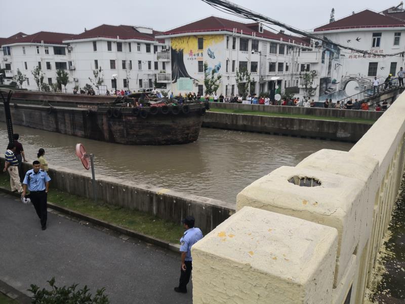 梅雨季节水位上涨,一条运输船在通过桥梁时因棚高被卡于桥下