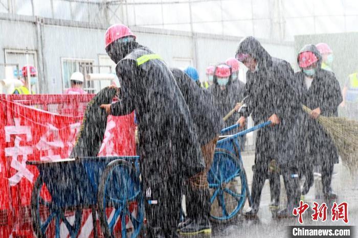 为了提升项目防汛抢险救灾实战能力,确保安全生产,一家央企用消防车模拟出突降暴雨的情形,来进行应急演练。 唐基真 摄