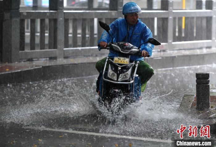 6月2日,福州外卖骑手经过积水路面。 张斌 摄