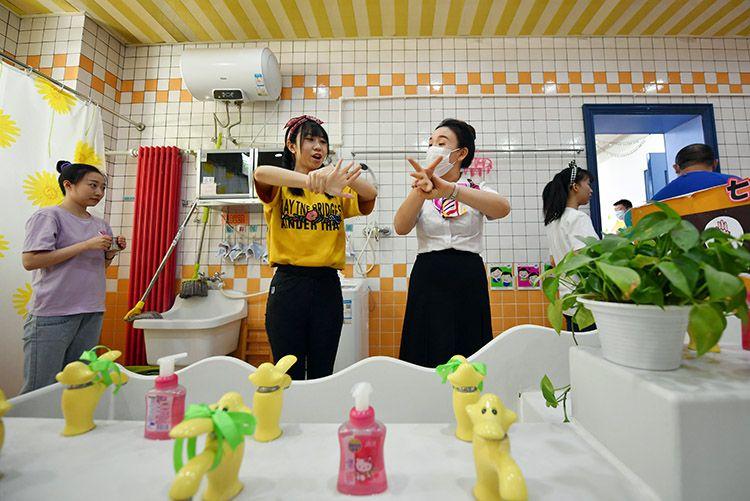 """教师带领""""小朋友""""一边唱《七步洗手歌》,一边洗手。"""