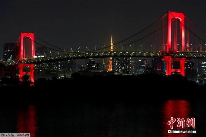 """6月2日,鉴于疫情有扩大趋势,东京都政府决定发布""""东京警报""""以唤起民众注意。图为东京地标性建筑彩虹桥亮起红灯。"""