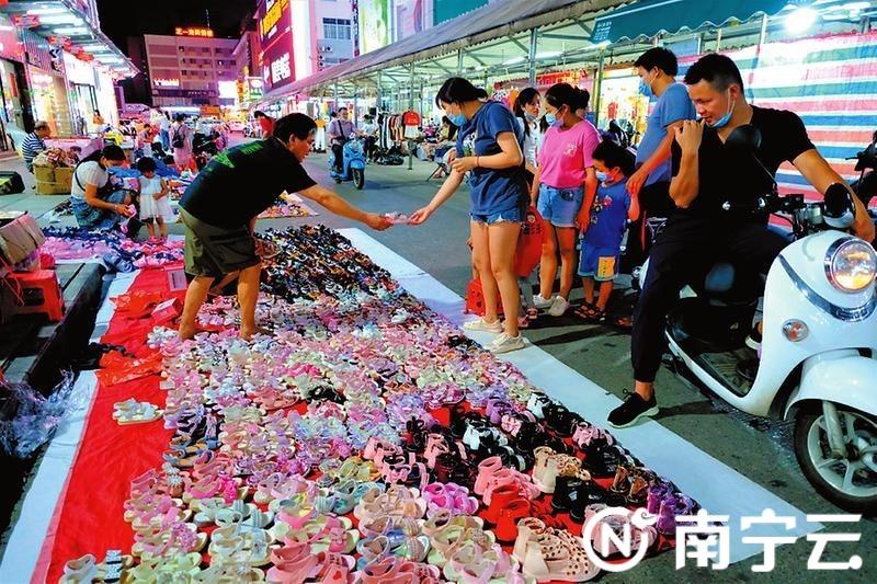 在淡村商贸城,市民正给自家宝贝挑一双漂亮鞋子。