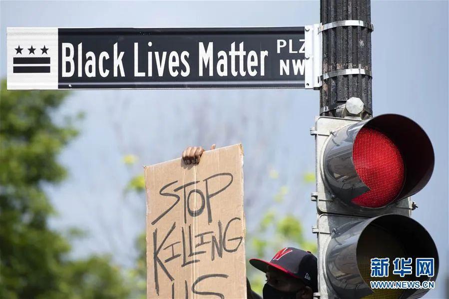 """▲6月6日,一名男子手举""""停止杀害我们""""的标语在美国华盛顿白宫附近的""""黑人的命也是命广场""""路牌下参加游行活动。新华社记者 刘杰 摄"""