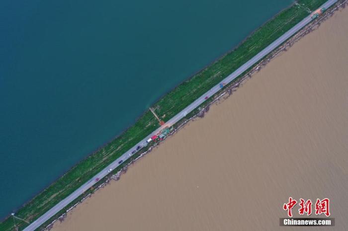 7月12日下午,航拍位于鄱阳湖东岸的江西鄱阳县珠湖联圩,一侧为清澈的鄱阳湖内湖珠湖,一侧为因暴雨变浑浊的鄱阳湖外湖,呈现一堤之隔泾渭分明的景观。 中新社记者 刘占昆 摄