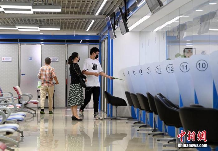資料圖:市民在位于北京的英國簽證申請中心遞交簽證相關材料。 中新社記者 侯宇 攝