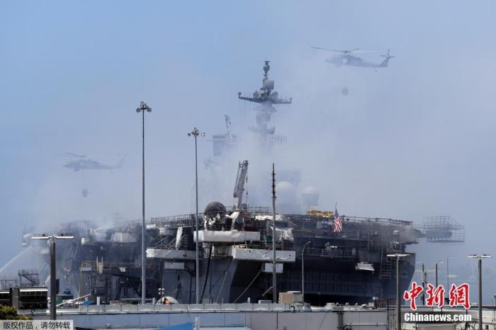 """当地时间7月13日,美国海军两栖攻击舰""""好人理查德""""号大火进入第二天。图为""""好人理查德""""号舰体冒出滚滚浓烟。"""