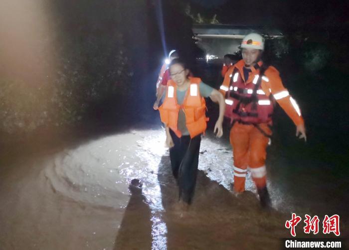 救火员护送群众趟水转移。泸州消防提供