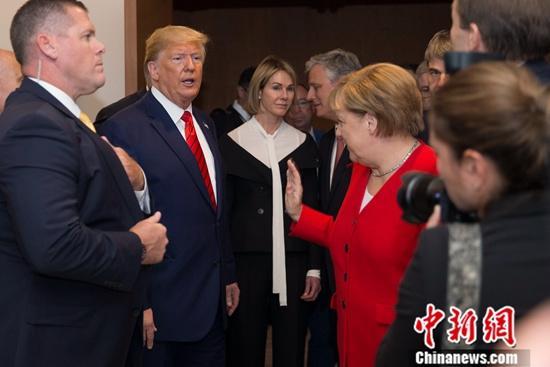 资料图:美国总统特朗普与德国总理默克尔进行交流。中新社记者 廖攀 摄