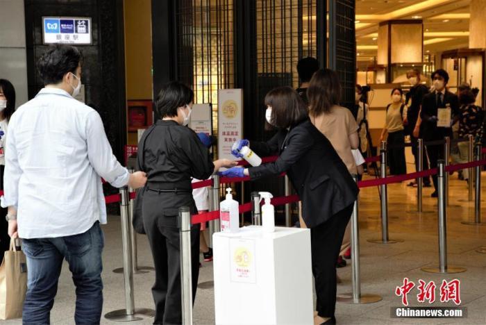 """当地时间6月6日,日本东京都发布新冠肺炎疫情""""东京警报""""后的首个周末,虽然当地已进入疫情恢复阶段,但各商场仍采取多种防疫措施严阵以待。图为东京某商场为进店顾客进行消毒。 中新社记者 吕少威 摄"""