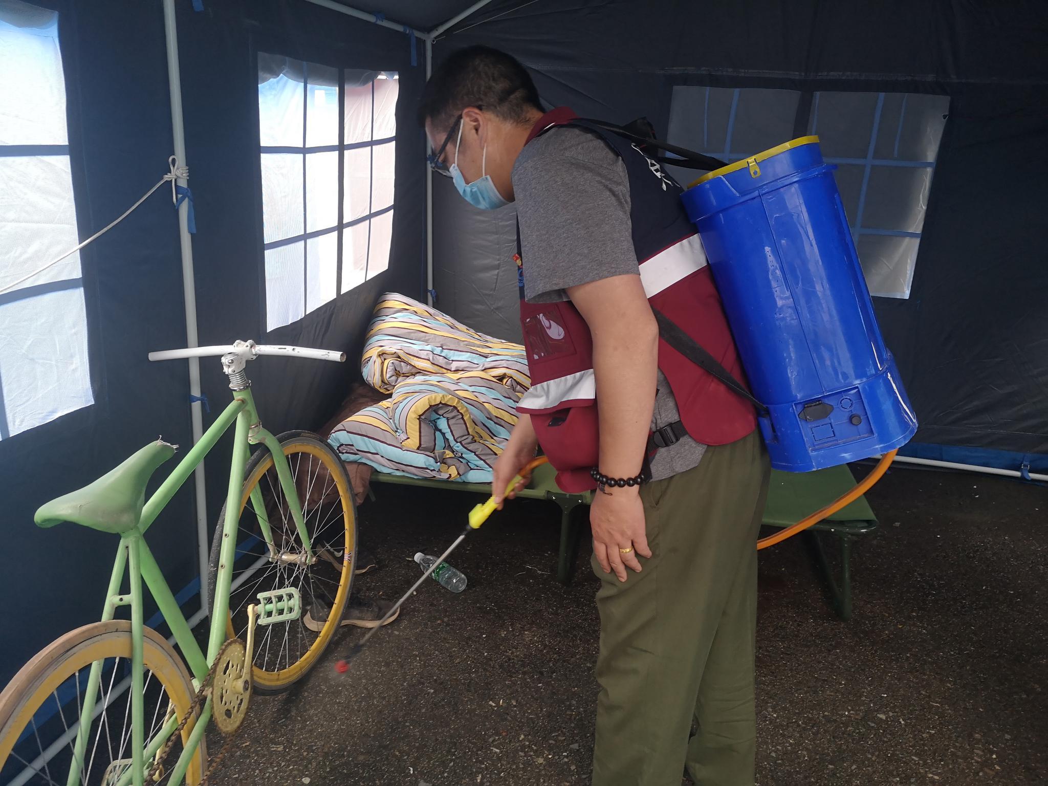 6月30日,庄韬在原曹古乡乡政府门前的安置帐篷内消毒。新京报记者 李桂 摄