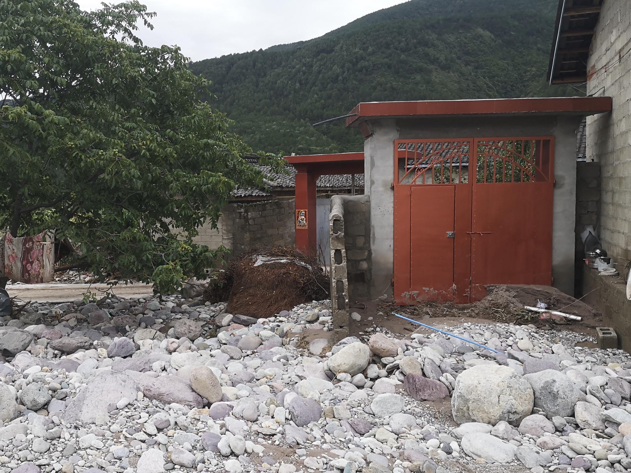 大堡子村内的一处民房,三面墙都被洪水冲走了,只剩下一扇红色铁门。新京报记者 李桂 摄