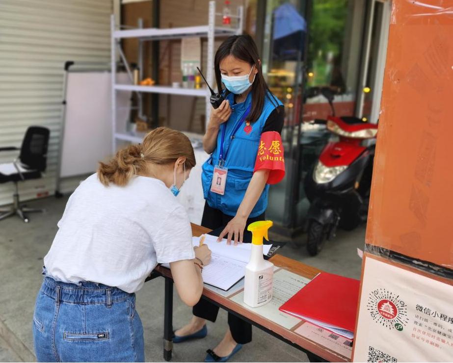 7月1日,平静桥街道丽湾社区书记杨霞在卡口执勤查抄挂号收支职员康健码。
