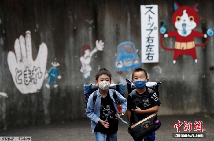 当地时间7月16日,日本东京,孩子们戴着口罩结伴上学。