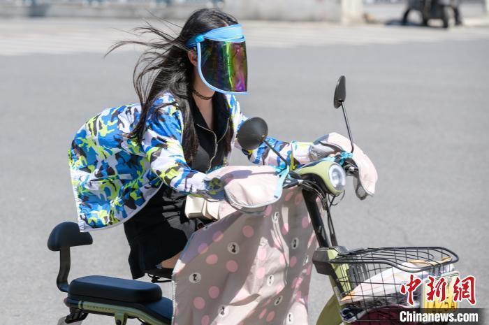 """资料图:7月13日,高温笼罩下,福州市民""""全副武装""""骑行在街头。 李南轩 摄"""