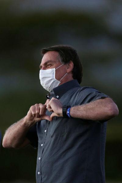 """感染新冠的巴西总统博索纳罗会见支持者,并向支持者""""比心""""致意。(路透社)"""