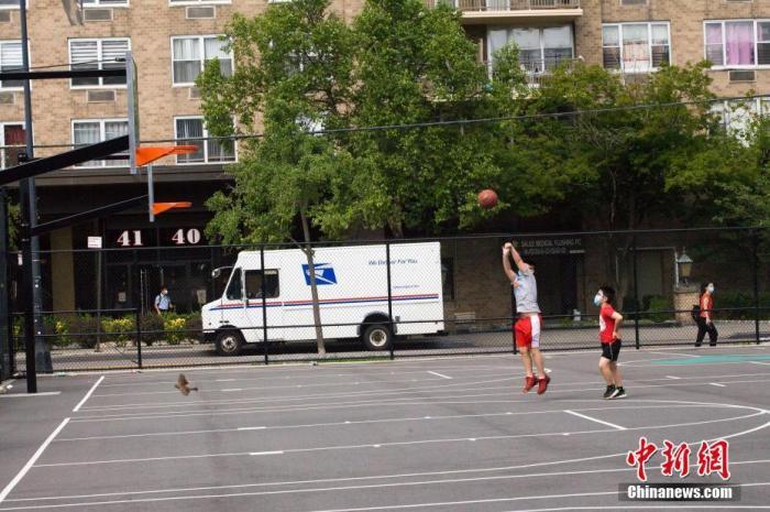 7月20日,纽约市进入4阶段重启。按规定,4阶段重启期间,市民可以进行低风险的室外艺术和娱乐活动。图为皇后区法拉盛一处社区体育场,两名少年正在打篮球。 中新社记者 马德林 摄