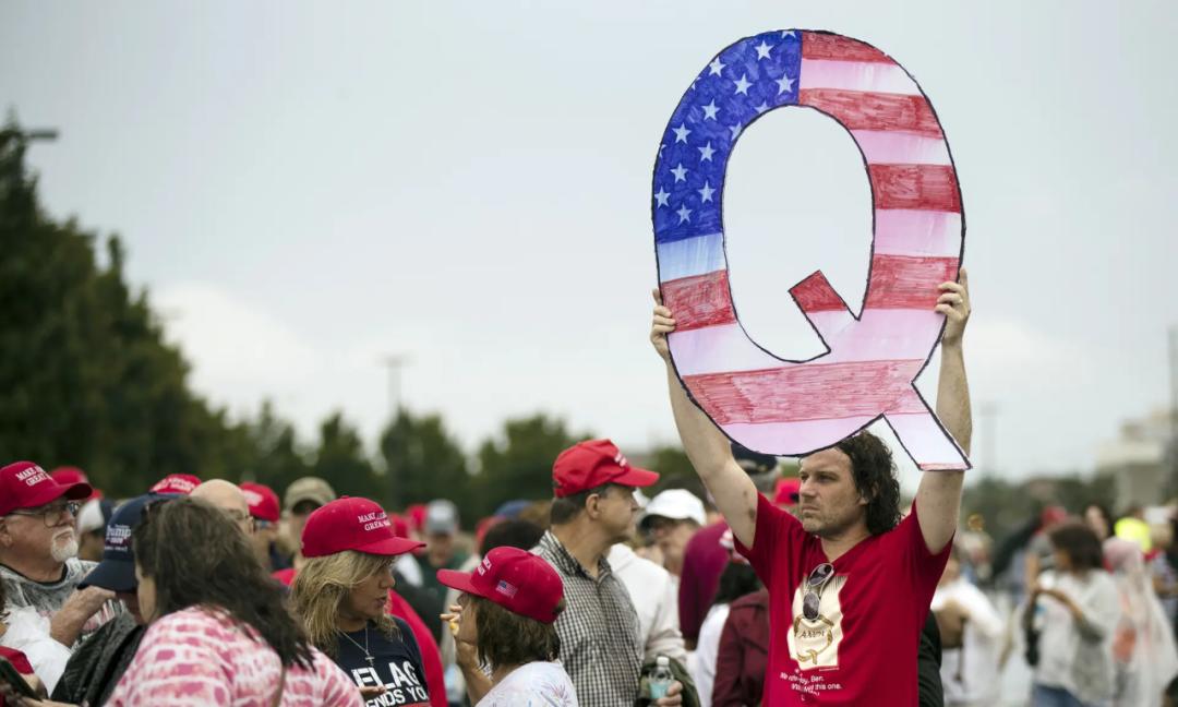 QAnon支持者在政治集会上举标牌(资料图)