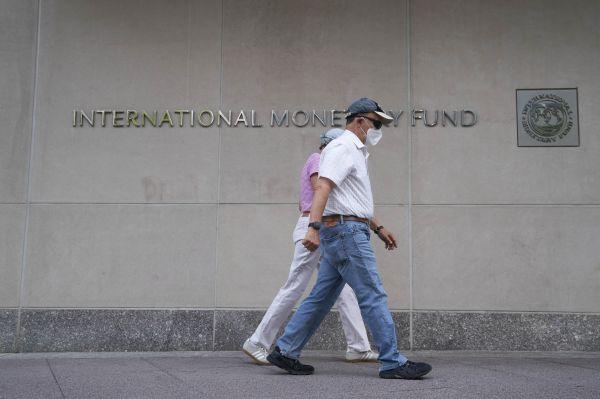 7月17日,在美国首都华盛顿,行人从国际货币基金组织总部大楼前经过。(新华社)