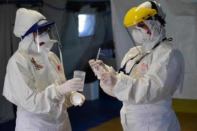 资料图。今年3月,在意大利博洛尼亚一家医院的分诊帐篷里,医务人员采集疑似新冠肺炎患者的生物检测样本图据新华社