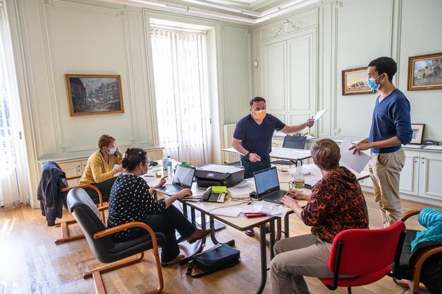 资料图。今年3月,在法国塞纳-马恩省的马恩河畔托里尼,工作人员在市政厅内临时设立的新冠肺炎电话咨询中心工作图据红星新闻