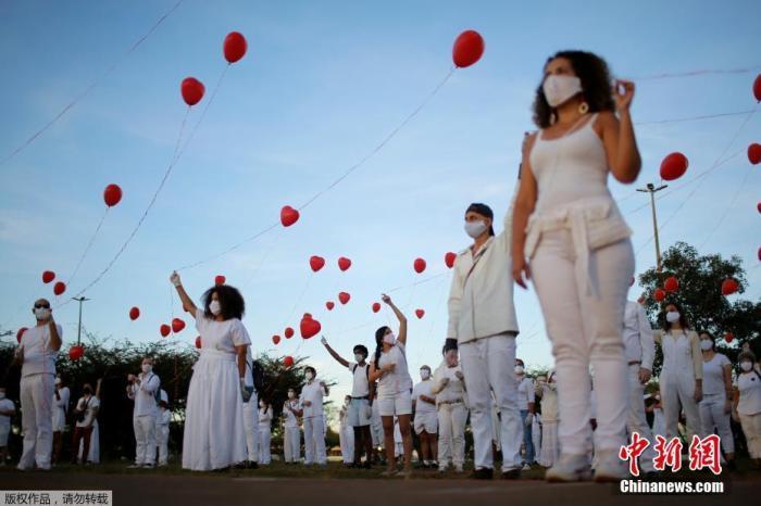 当地时间6月1日,巴西首都巴西利亚,艺术家们手持红色气球悼念在新冠肺炎疫情中不幸离世的人们。