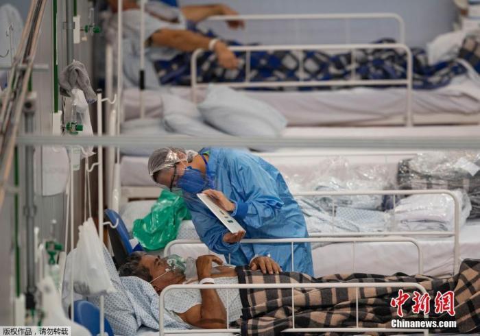 资料图:圣保罗郊区方舱医院内,医护人员和患者交流。