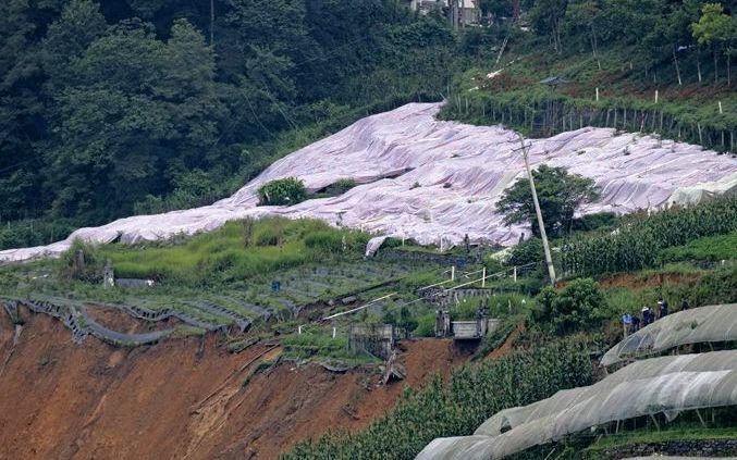 7月23日,工作人员在滑坡地段上方铺上油布,防止出现新的滑坡。新京报记者 陶冉摄
