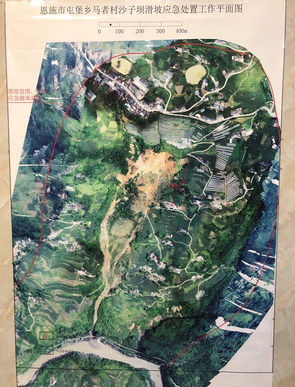 7月23日,挂在村委会办公室的滑坡航拍图,危险区域用红线标出。新京报记者 向凯 摄