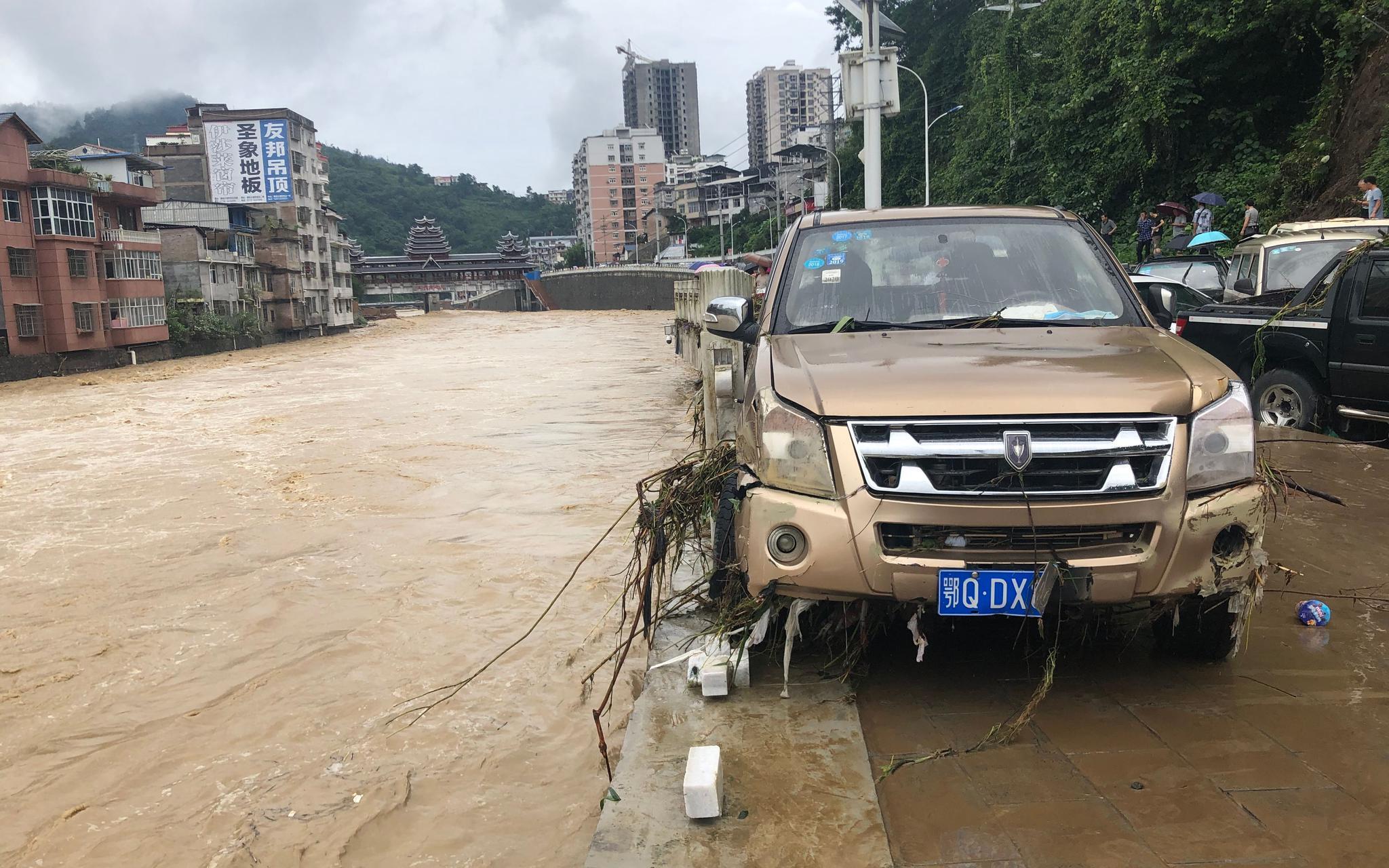 7月26日,建始县广润河产生大水,几十台车辆被淹,岸边雕栏损毁,不少车辆被突入河中。新京报记者 向凯 摄
