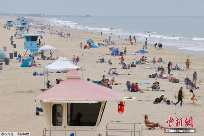 图为美国加州亨廷顿海滩上的游客。